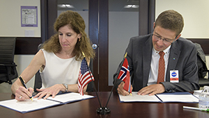 Karen Feldstein, NASA Deputy Associate Administrator for International and Interagency Relations and Per Erik Opseth, Director, Geodetic Institute of the Norwegian Mapping Authority signing the agreement.